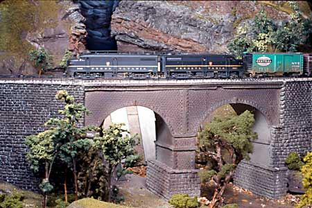 PRR FA's #9600 and #9601 lead an afternoon freight over the stone arch bridge over the Thicket River.