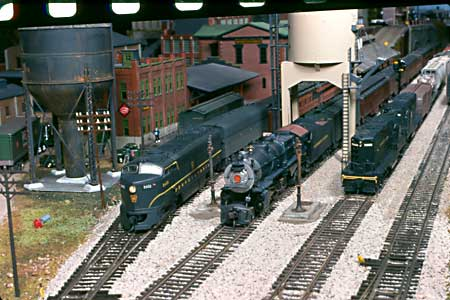 Two passenger trains are ready to depart the busy Mount Penn station, while two Geeps glide their manifest train out of town.