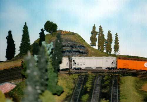 A slow freight passes the end of the yard near Briggs Hill